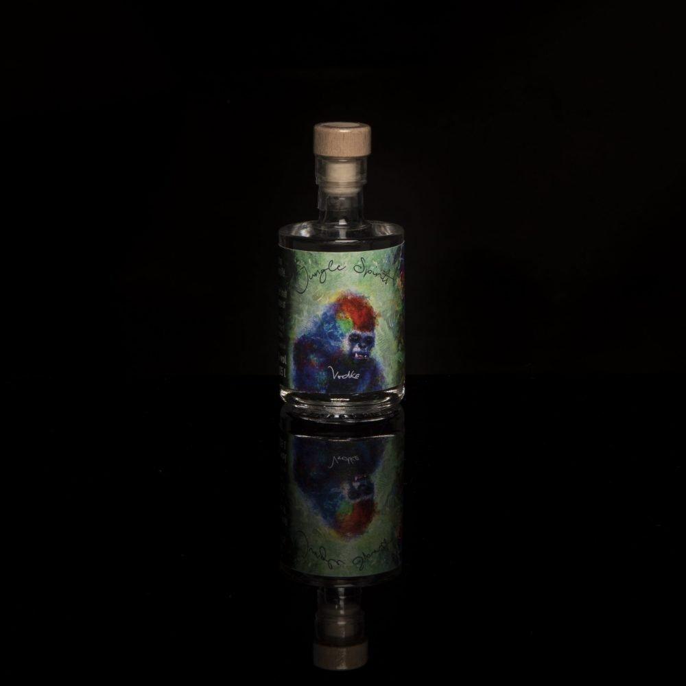 Miniaturflasche mit Gorillaetikett vor schwarzem Hintergrund.