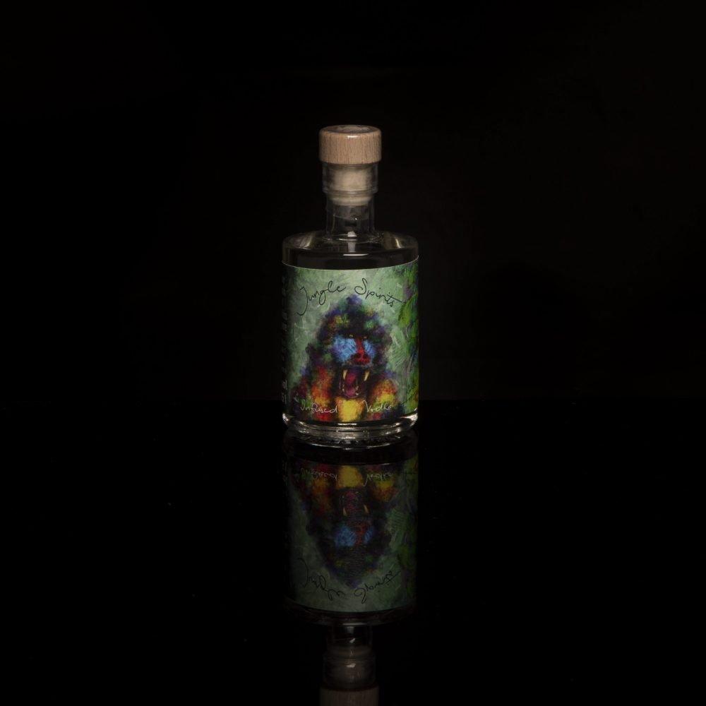 Kokos-Honigmelone als Miniaturflasche vor schwarzem Hintergrund.