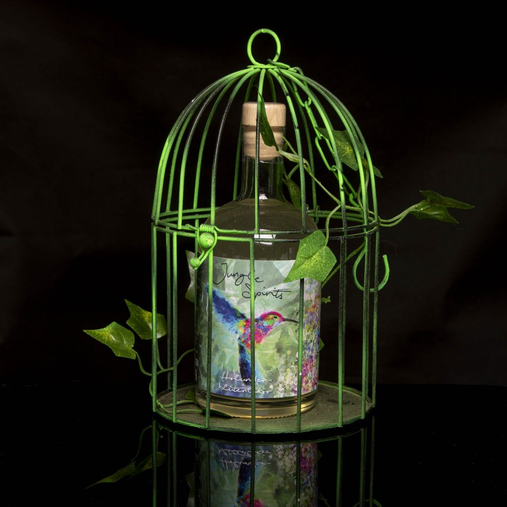 Produktbild von unserem Holunderblütenlikör in neongrünem Metallkäfig.