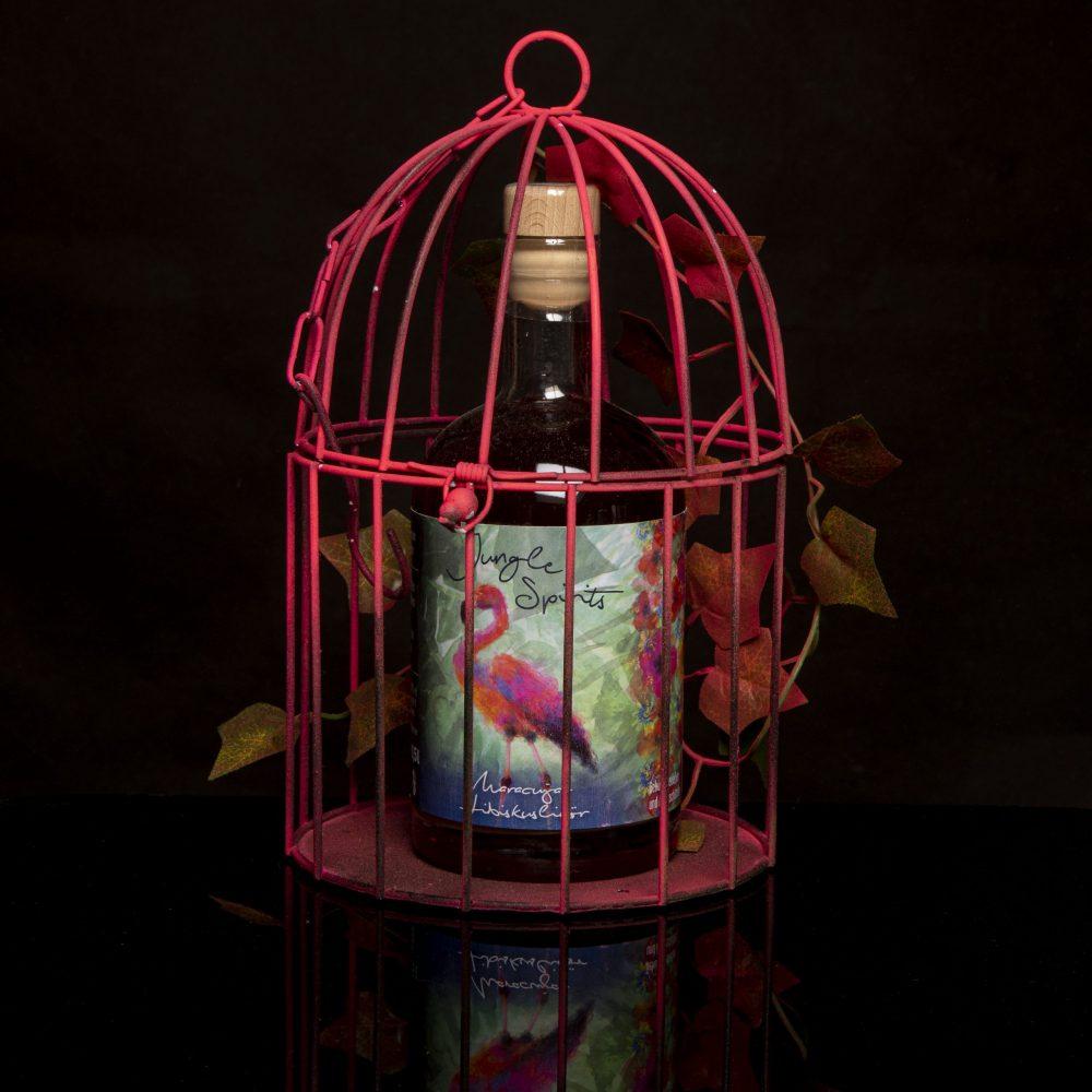 Produktbild unseres Maracuja-Hibiskus-Liköres. Bunter Flamingo in neonpinkem Metallkäfig.