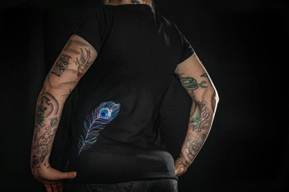 Schwarzes, fairgehandeltets Tshirt mit pastellfarbenener Feder-Stickung auf der Rückseite.