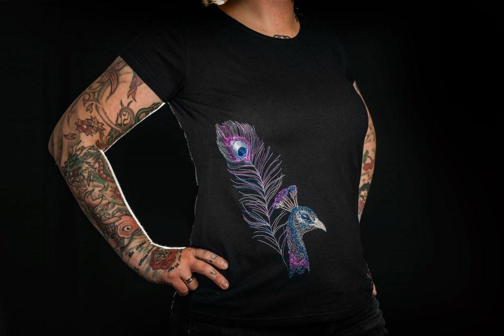 Schwarzes, fairgehandeltets Frauen-Tshirt mit pastellfarbenener Pfauen-Stickung.