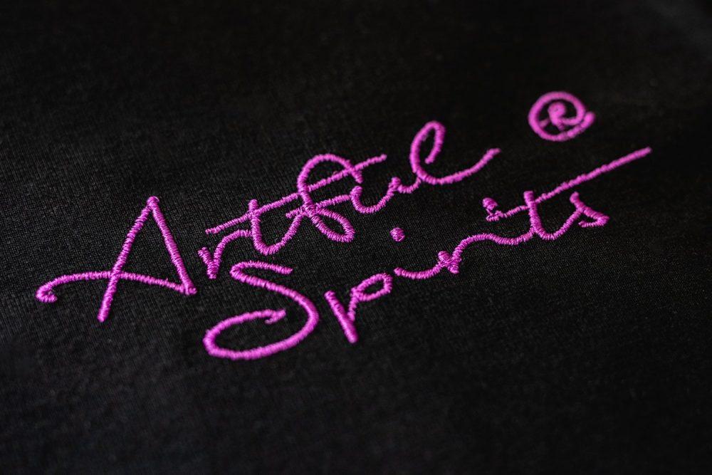 T-Shirt Damen, Artful Spirits Schriftzug gestickt in lila.